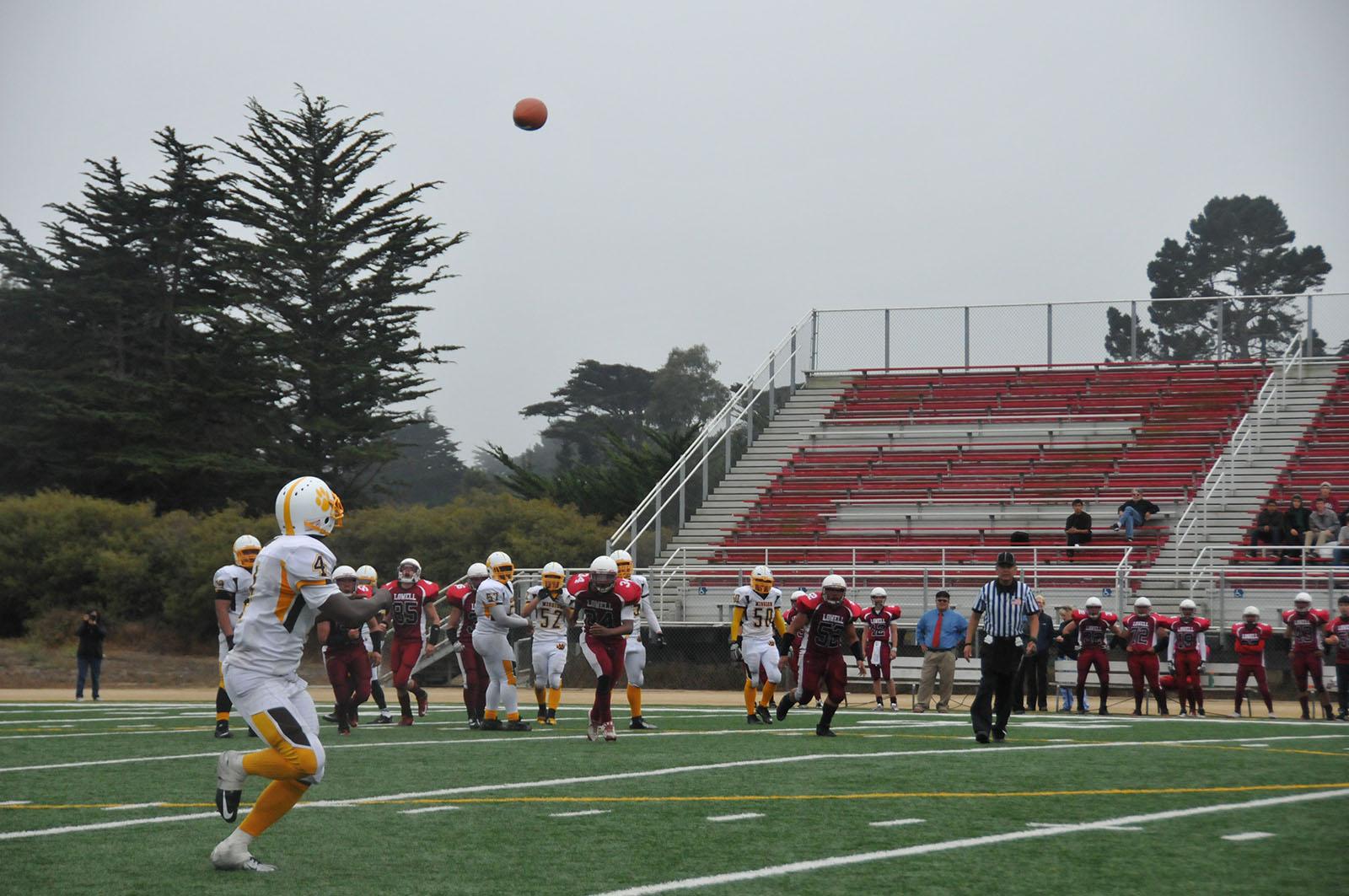 A football player runs to catch a ball.