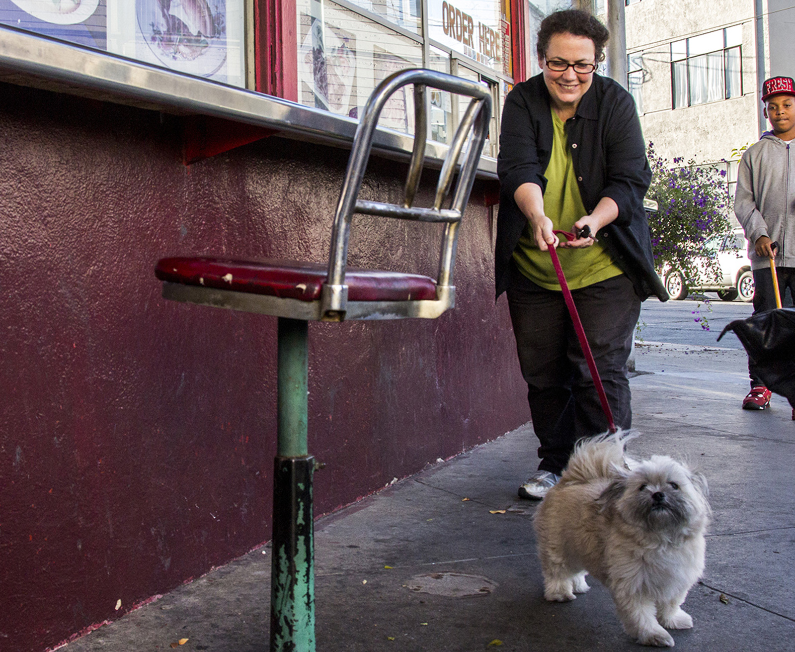 A lady tries to restrain her very happy puppy dog on a red leash.
