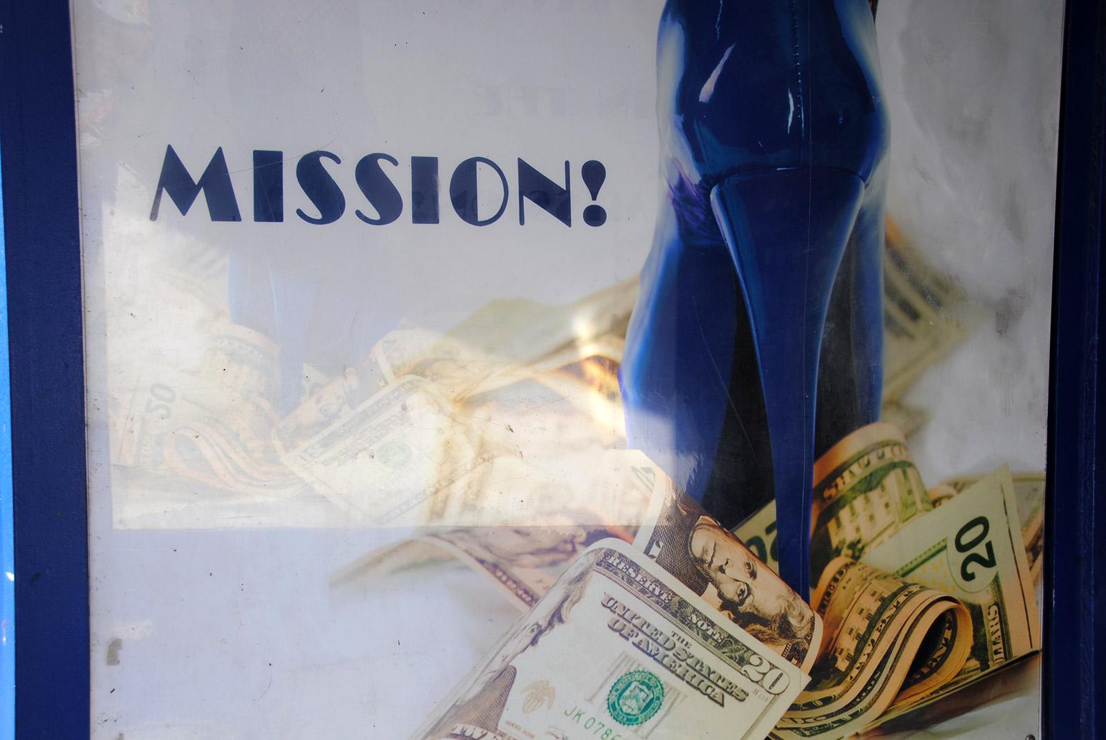 Image shows a blue stilleto standing on money