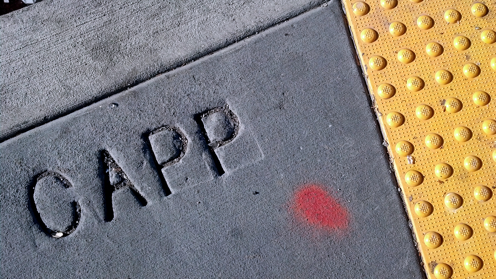 "A close-up of ""Capp"" written on the sidewalk."