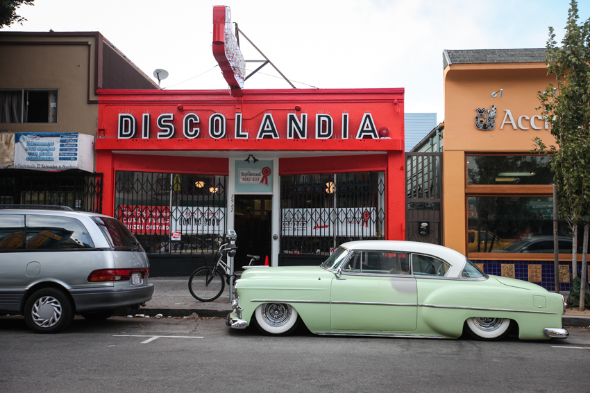 An old classic vintage car parks in front of Discolandia building