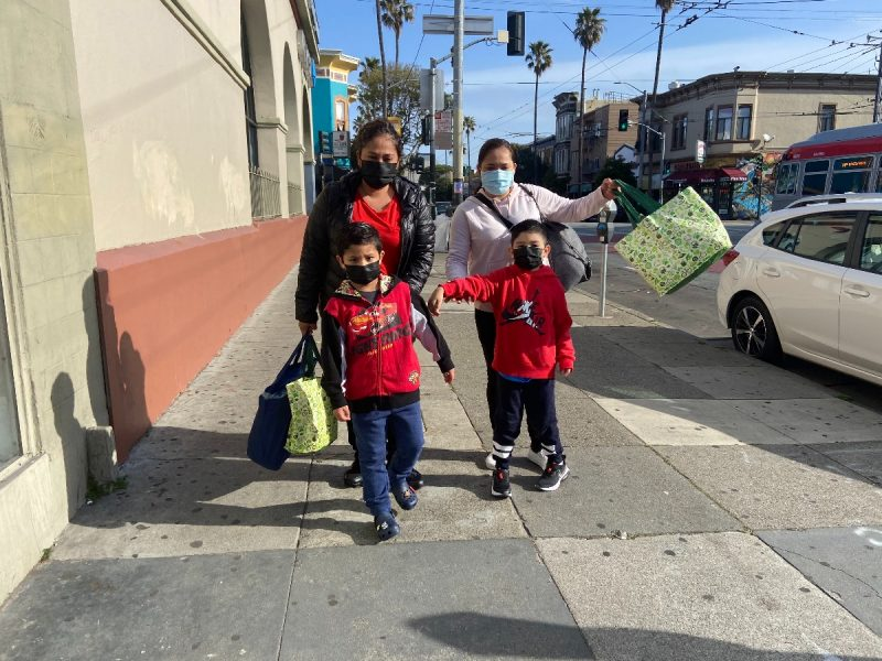 FIRST DAY OF SCHOOL, SAN FRANCISCO: Adriana Miranda (left), and her sister Claudia Miranda (right) walk their sons Cesar and Sebastian, both 5, to kindergarten at Zaida T. Rodriguez Early Education School. The sisters say they are excited to have their children back in school. Mission schools open first day during the pandemic. Image shows parents bringing their children back to school. Photo by Clara-Sophia Daly.