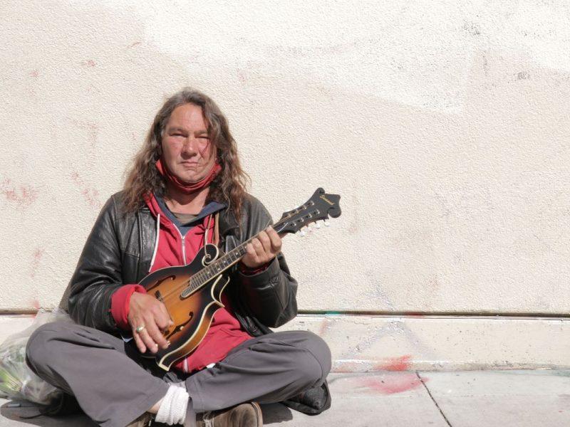 Max Johnson sits on the sidewalk on Bartlett Street playing his mandolin