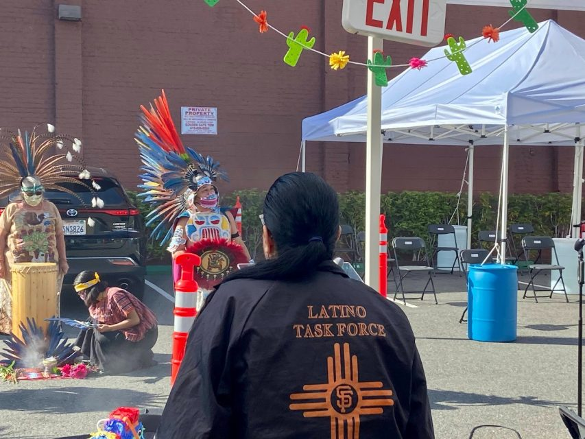 Valerie Tulier-Laiwa, of the Latino Task Force, watches the Aztec dancers perform at the opening ceremony of the second vaccination site in the Mission. Residents can now get a vaccination at one of the two sites seven days a week. Photo by Clara-Sophia Daly. Covid vaccination site Mission.