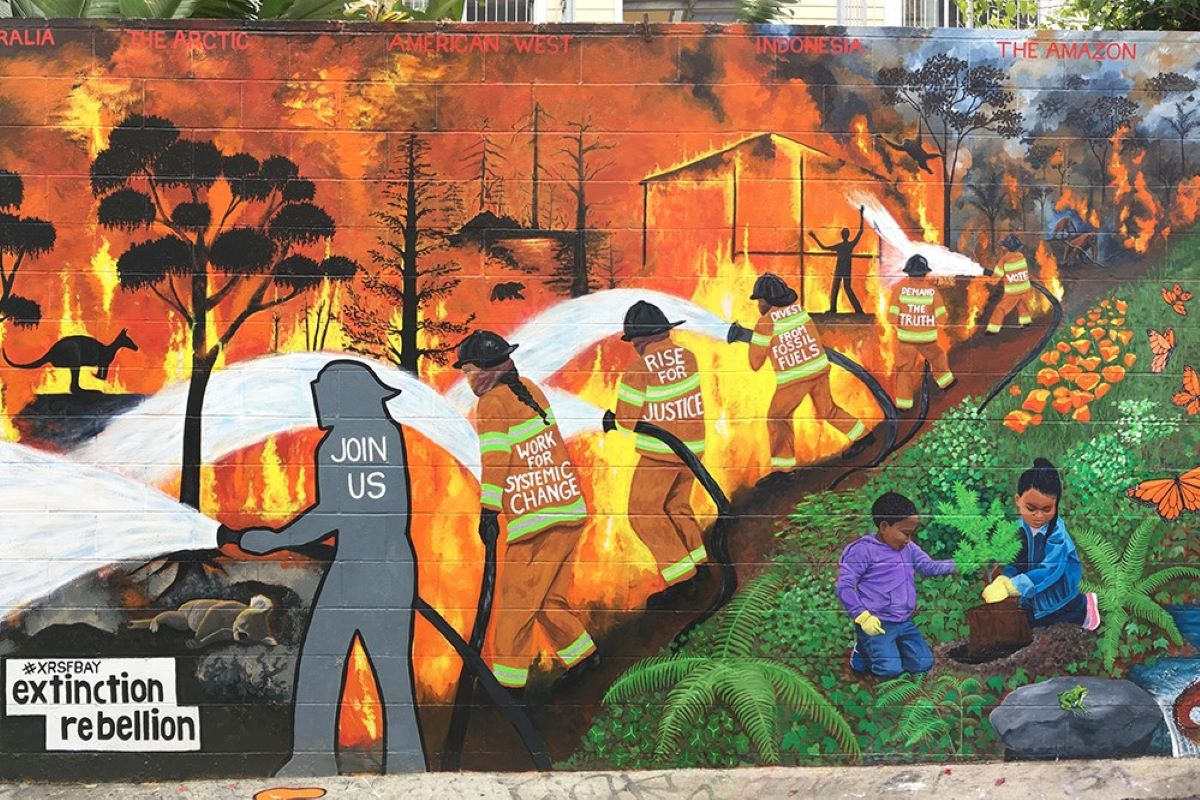 The new mural on clarion alley shows a line of firefighters holding a fire at bay from children playing in a lush forest landscape.