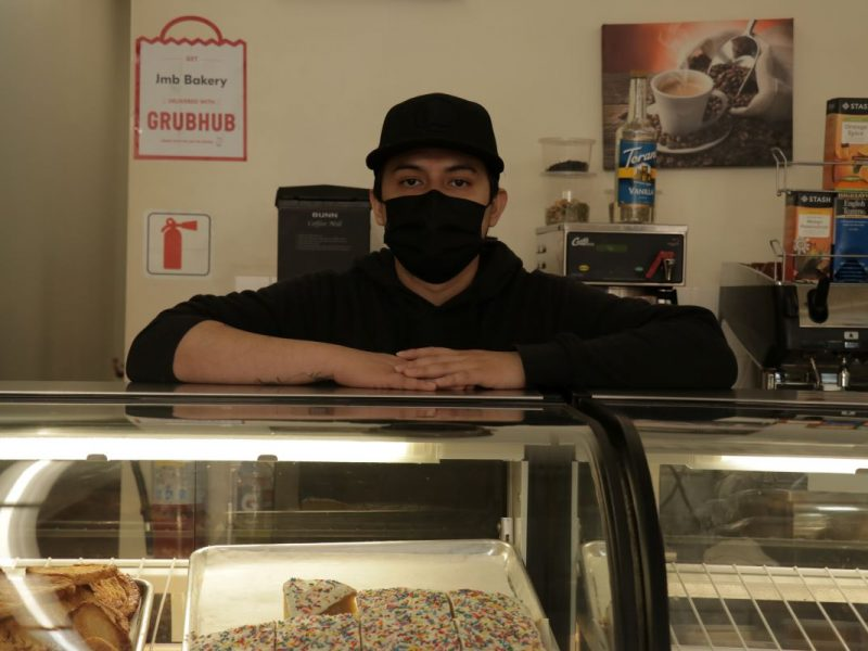 Eduardo Daniel Mooyah stands behind the counter at JMB Bakery on 16th Street. Photo by Juan Carlos Lara.