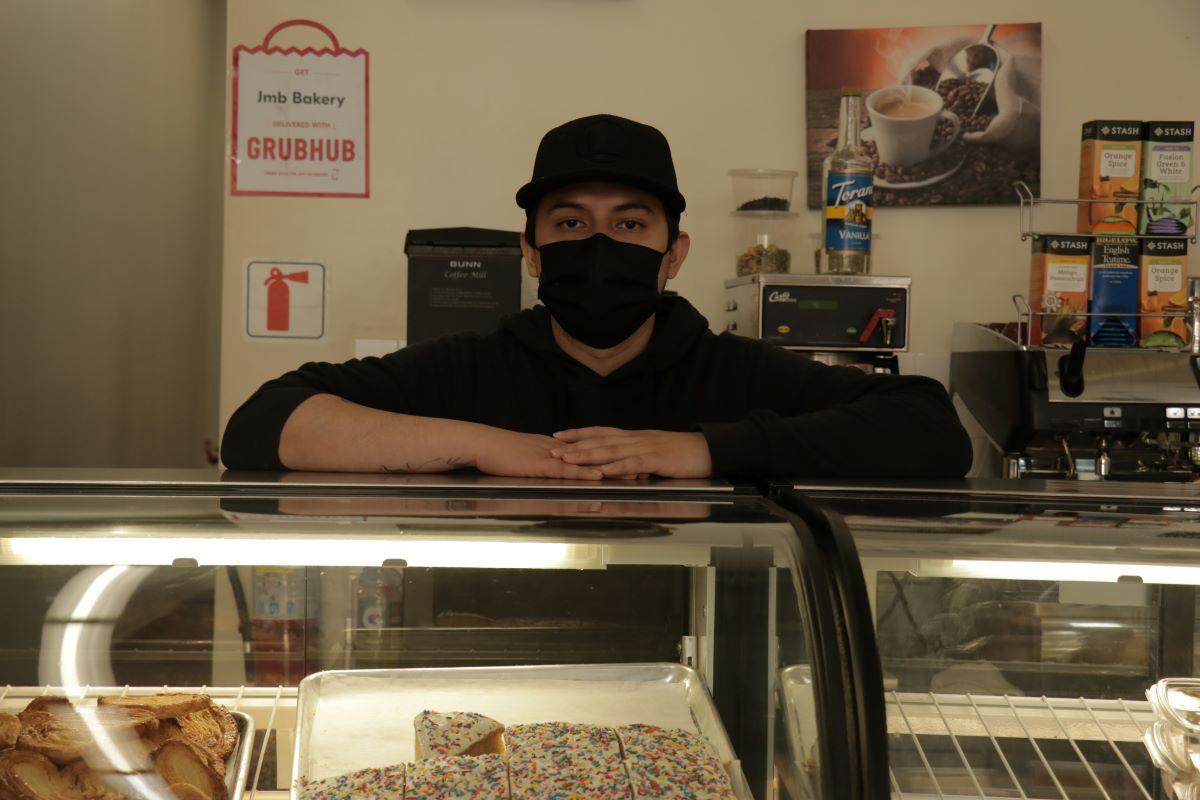 Eduardo Daniel Mooyah stands behind the counter at JMB Bakery on 16th Street. Photo by Juan Carlos Lara.